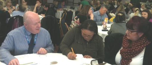 photo of staff member working with carers at a table at the carers matter event on 17th march