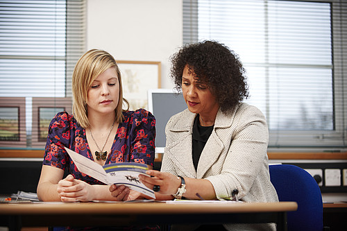 Female Personal Assistant and Female Manager looking at Leaflets in an office. Two women sitting side by side, making plans. Supported working. Care Sector workforce. Staff training and development. Review. Meeting.