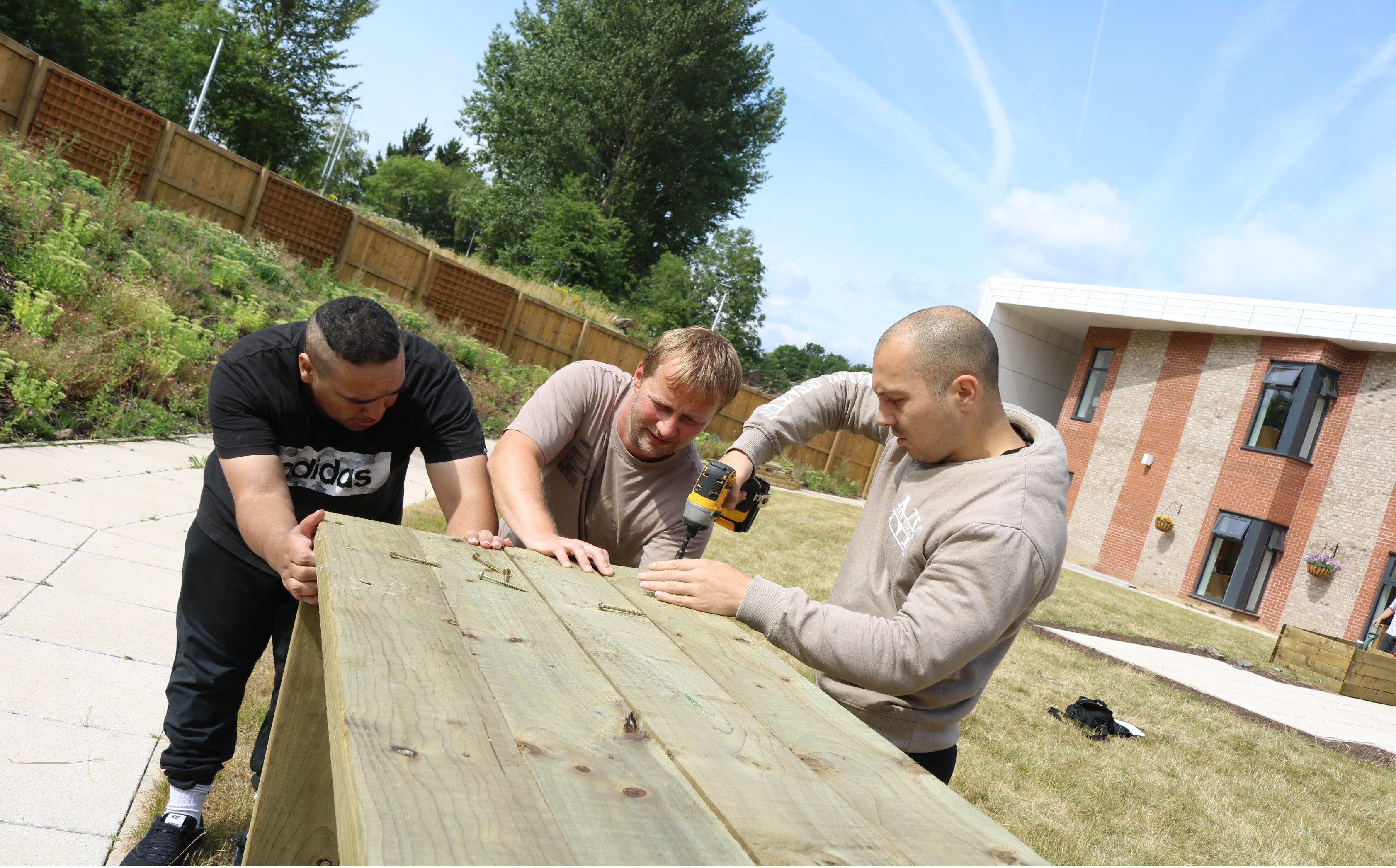 Staff and service users build a raised bed for the new garden at Crumpsall Vale Intermediate Care Unit