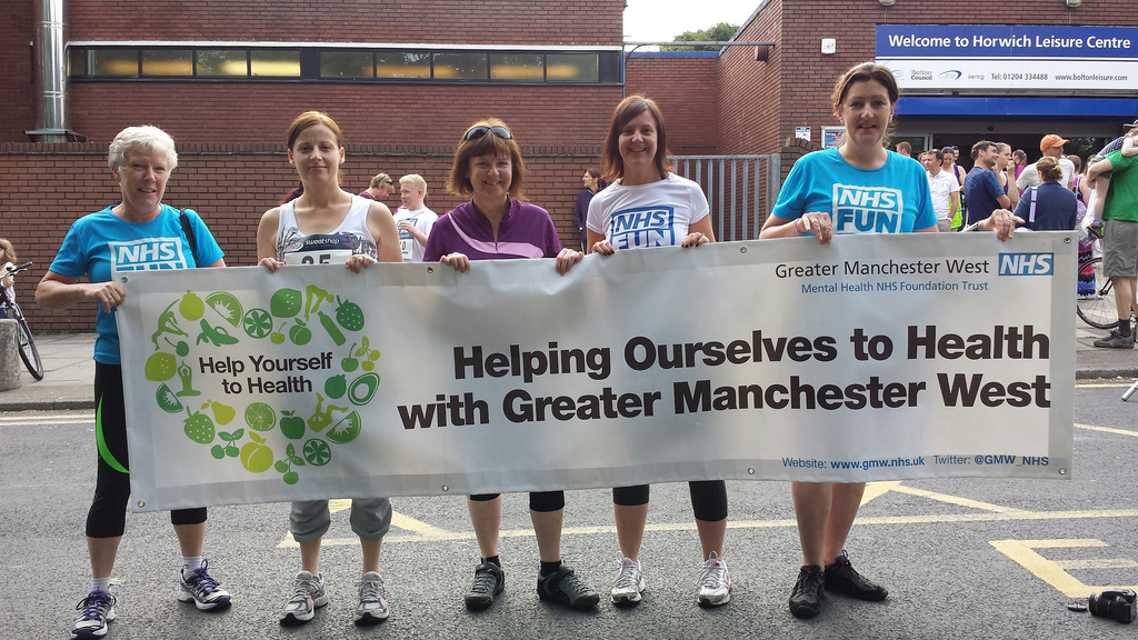GMW staff at NHS Fun Tri 2013 holding banner reasing 'Helping Ourselves to Health with Greater Manchester West'